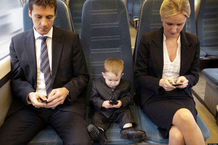 Взрослые и ребенок с телефонами