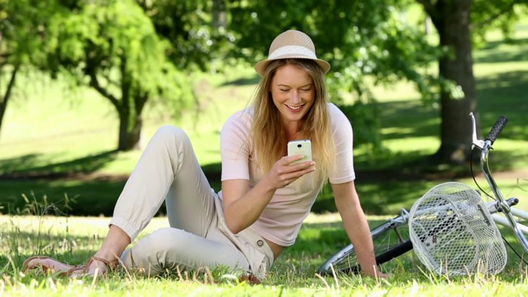 stock-footage-pretty-girl-using-smartphone-beside-her-bike-in-the-park-on-a-sunny-day
