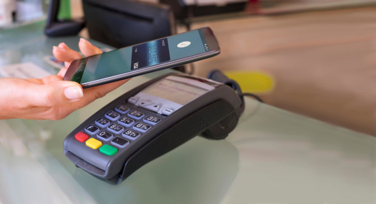 Female paying with NFC technology on mobile phone, beautician