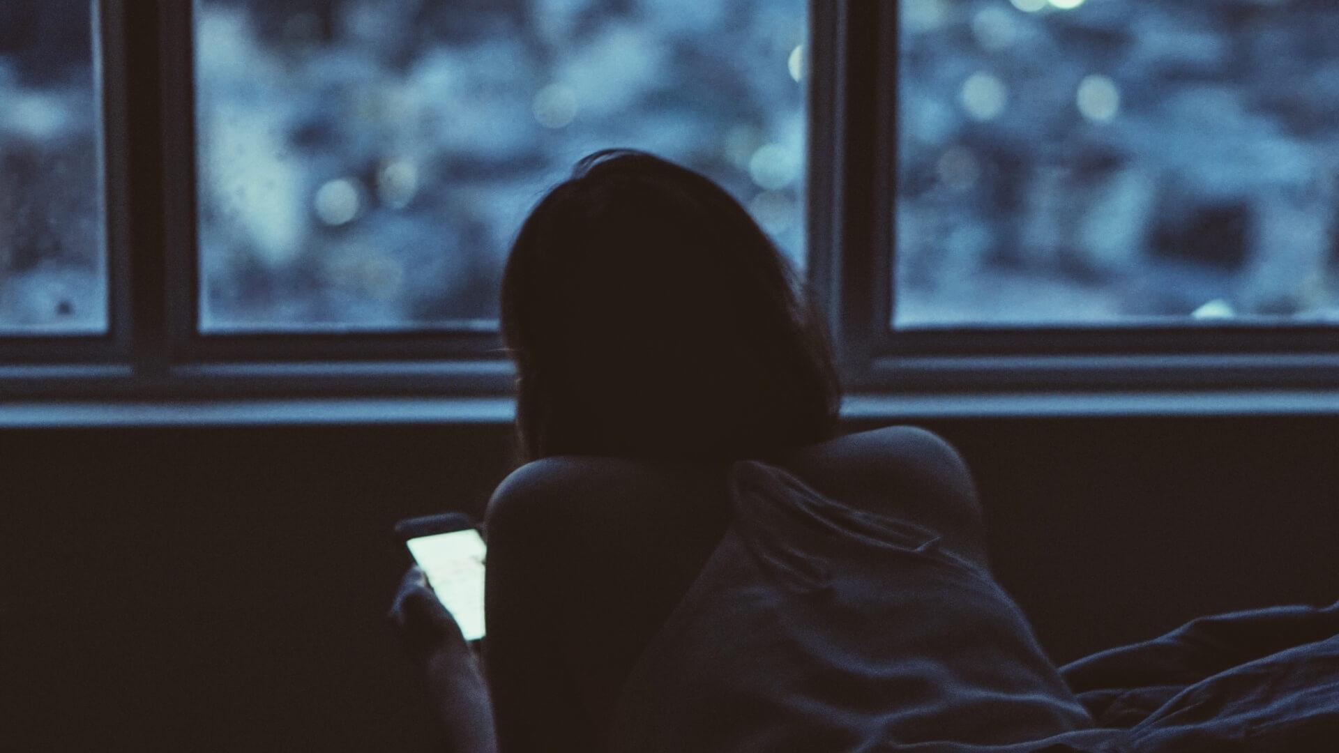 Девушка с телефоном вечером у окна